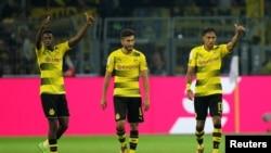 Ousmane Dembele de Dortmund, à gauche, célèbre avec ses coéquipiers Pierre-Emerick Aubameyang et Nuri Sahin après le deuxième but de leur équipe contre FC Bayern Munich lors de la Supercoupe DFL à Dortmund, Allemagne, 5 août 2017.
