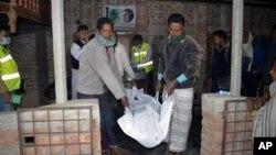 Les services de secours enlèvent un corps après une explosion à Bagmara, district Rajsahi, le Bangladesh, 25 décembre 2015.