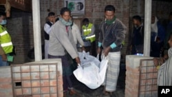Men remove the body of a suspected suicide bomber after an explosion was touched off at a mosque of a minority Ahmadiya Muslim sect, in Bagmara, Rajsahi district, Bangladesh, Dec. 25, 2015.