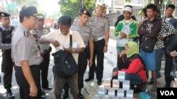 Pemeriksaan dan peringatan penukaran uang di pinggir jalan Surabaya untuk menghindari perdagangan uang palsu. (VOA/Petrus Riski)