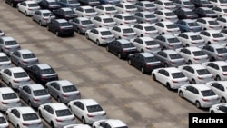 FILE - A man walks among cars which are ready for export at the port of Taipei, northern Taiwan, April 16, 2014.
