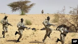 Dans cette photo du 18 mars 2004, des soldats maliens s'entrainent aux côtés des forces spéciales américaines près de Tombouctou, dans le cadre de l'Initiative pan-sahélienne américaine.