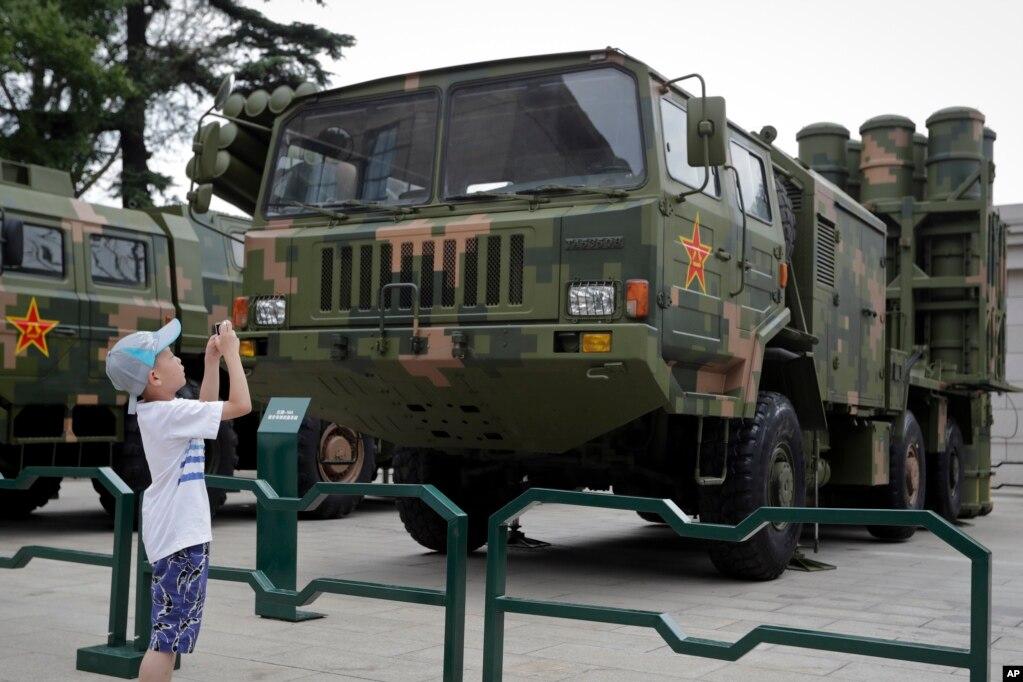 在北京军事博物馆,儿童给中程防空导弹发射器和运载车拍照(2017年7月27日)。为纪念中国人民解放军(People's Liberation Army)建军90周年,北京军事博物馆展览了一些新式武器。