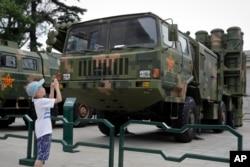 在北京軍事博物館,兒童在中程防空導彈發射器和運載車外拍照