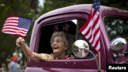 FILE - A woman waves an American flag as she rides in an antique pickup truck through Barnstable Village on Massachusetts' Cape Cod during the community's annual Independence Day parade, July 4, 2015.