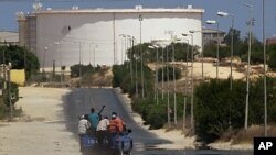 A truck carrying Libyan rebel fighters drives towards the Zawiya oil refinery, August 17, 2011