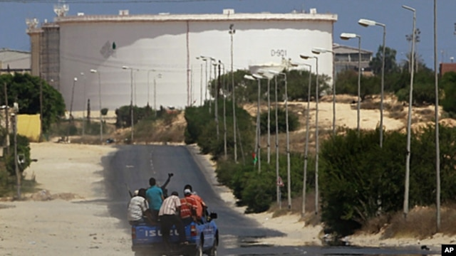 A truck carrying Libyan rebel fighters drives towards the Zawiya oil refinery in Zawiyah, August 17, 2011