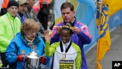 Meya wa Boston Marty Walsh akimvalisha taji Caroline Rotich wa Kenya l 20, 2015 in Boston. (AP Photo/Elise Amendola)