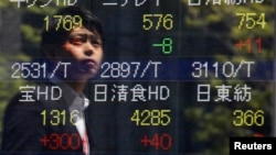 A pedestrian is reflected on a stock quotation board showing stock prices outside a brokerage in Tokyo May 8, 2013.