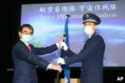 Menteri Pertahanan Jepang Taro Kono (kiri) menyerahkan bendera unit Skuadron Operasi Ruang Angkasa kepada kepala unit Toshihide Ashiki (kanan), pada upacara peluncuran di Kementerian Pertahanan di Tokyo, Jepang, Senin.