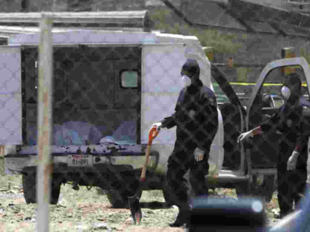 Police stand near a coroner's car containing bodies found in a mass grave in Durango, April 20, 2011