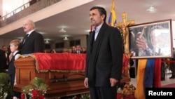 Presiden Iran Mahmoud Ahmadinejad berdiri di dekat peti jenazah Presiden Venezuela Hugo Chavez dalam upacara pemakaman di Caracas, Jumat (8/3).