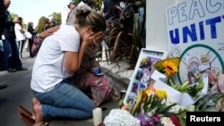 FILE - A woman reacts at a make shift memorial outside the Al-Noor mosque in Christchurch, New Zealand, March 23, 2019.