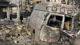 Residents walk past a damaged emergency vehicle in Aleppo, Syria, January 1, 2013.