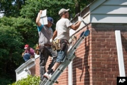 These workers repair the roof of a house in the U.S. state of Virginia, June 2014. (AP Photo/J. Scott Applewhite)