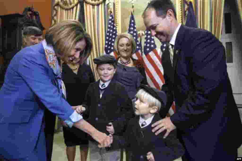 House Speaker Nancy Pelosi, left, shakes the hand of Preston Stutzman, 4, with his brother Payton Stutzman, 9, mother Christy Stutzman, and father Rep. Marlin Stutzman, R-Ind., before a ceremonial swearing-in for Stutzman at the Capitol in Washington, Tue