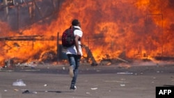 FILE - Zimbabwe's opposition supporters set up a burning barricade as they clash with police during a protest for electoral reforms, Aug. 26, 2016 in Harare, Zimbabwe.