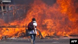 FILE: Zimbabwe's opposition supporters set up a burning barricade as they clash with police during a protest for electoral reforms, Aug. 26, 2016 in Harare, Zimbabwe.