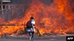 Abashigikiye abatavuga rumwe na Reta muri Zimbabwe bariko baturira bariyere, igihe bariko bahangana n'igipolisi, ku murwa mukuru, Harareb, ku musi wa gatanu, italiki 26, umwaka w'i 2016.