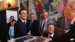 Presiden Perancis Emmanuel Macron, kiri, bersalaman dengan petugas pemilu setelah memberikan suaranya pada putaran kedua pemilu parlemen Perancis di Le Touquet, Perancis utara, Minggu, 18 Juni 2017. (Christophe Archambault/Pool Photo via AP)