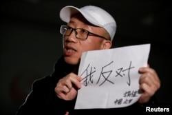 """2018年2月28日,在北京接受路透社采访时,中国维权人士胡佳手持标语""""我反对""""。(2018年2月28日)"""