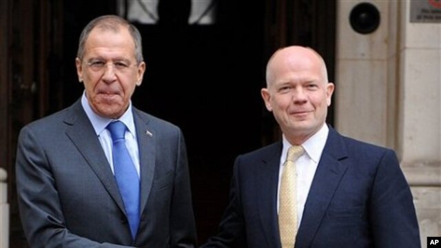 British Foreign Secretary William Hague, right, greets Russian Foreign Minister Sergei Lavrov as he arrives at the Foreign and Commonwealth Office for a bilateral meeting, in London, February 15, 2011