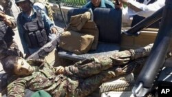 The body of an Afghan national army soldier lies in an army vehicle after he opened fire on U.S. troops, in the compound of the provincial governor, Jalalabad, east of Kabul, Afghanistan, April 8, 2015.