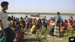 孟加拉国的一些村民在船倾覆的现场附近等待