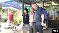 Chum Mey, former victim of S-21 prison, takes a photo with tourists inside the Tuol Sleng Genocide Museum, in Phnom Penh, January 16th, 2020. (Hul Reaksmey/VOA)