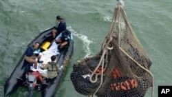 Những túi đựng thi thể của hành khách trên chuyến bay 8501 của AirAsia Flight được đưa lên tàu hải quân của Indonesia ngoài khơi Pangkalan Bun, ngày 3 tháng 1, 2015.
