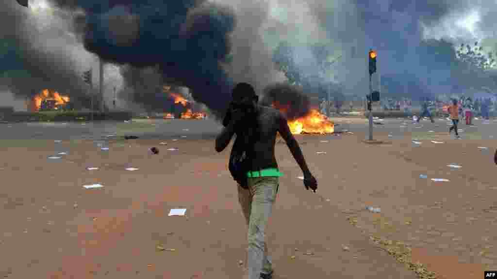 Un manifestant essuie son visage devant le parlement alors que des voitures et des documents brûlent à l'extérieur, à Ouagadougou le 30 octobre, 2014. Des centaines de manifestants en colère au Burkina Faso ont pris d'assaut le parlement le 30 Octobre avant d'y mettre le feu en signe de protestation contre l'intention de modifier la Constitution pour permettre au Président Blaise Compaoré pour étendre son règne de 27 ans. AFP PHOTO / ISSOUF SANOGO