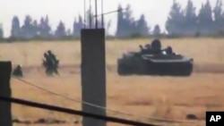 This image made from amateur video released by the Shaam News Network and accessed June 18, 2012, purports to show a Syrian military tank in Daraa, Syria.