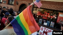 ay pride flag at a vigil outside The Stonewall Inn on Christopher Street