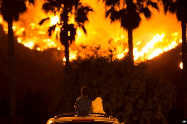 King Bass, 6, sits and watches a fire burn from on top of his parents' car as his sister Princess, 5, rests her head on his shoulder, Aug. 9, 2018 in Lake Elsinore, Calif.
