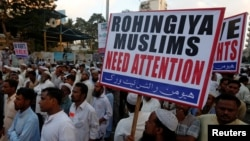A Human Rights Network activist holds a sign during a demonstration against the persecution of Rohingiya Muslims in Myanmar, in Karachi, Pakistan, Dec. 9, 2016.