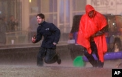 People run as weather sirens sound as a severe storm passes over downtown Dallas, Dec. 26, 2015.