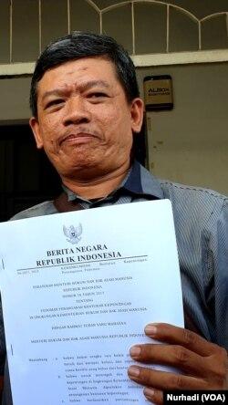 Tri Wahyu menunjukkan salinan Permen pedoman penanganan benturan kepentingan di lingkungan Kemenkum HAM. (Foto:VOA/Nurhadi)