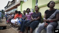 Voters sit and wait three hours after biometric identification machines had broken down, halting voting at a polling station, in Accra, Ghana, Friday, Dec. 7, 2012.