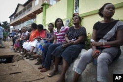 FILE - Voters wait three hours after biometric identification machines had broken down, halting voting at a polling station, in Accra, Ghana, Dec. 7, 2012.