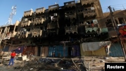 A boy looks at the site of a car bomb attack in a neighborhood of northern Baghdad August 11, 2013.