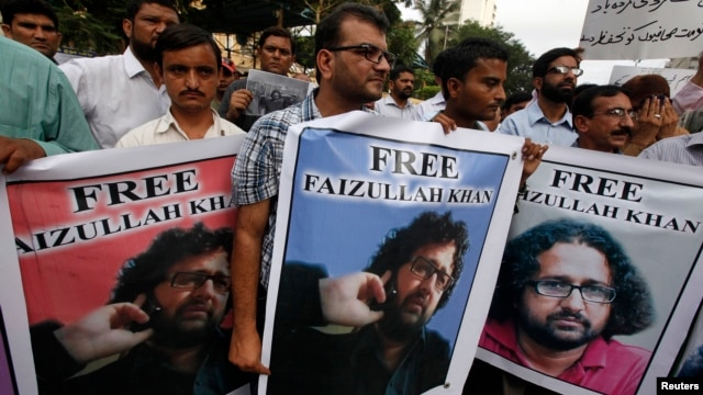 Pakistani journalists carry posters with the picture of local reporter Faizullah Khan, who was detained and imprisoned in Afghanistan, during a protest for his release outside the press club in Karachi, July 15, 2014.