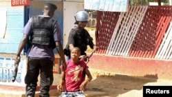 FILE - Policemen detain a protester during clashes in Lubumbashi, Democratic Republic of Congo, Nov. 10, 2015.