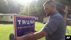 Bili Prater postavlja Trampov znak na svoju ogradu u Bič Kriku u Zapadnoj Virdžniji. Prater je rudar koji je bez posla više od godinu dana i sada radi za železnicu.