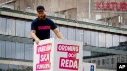 瑞典民粹主義政黨瑞典民主黨的成員2018年8月30日在斯德哥爾摩擺放競選標語。