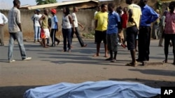 The body of a man killed is laid on a street in Bujumbura, Burundi after polls opened for the presidential elections Tuesday, July 21, 2015. Violence began in April after President Pierre Nkurnziza announced he would seek a third term in office, which the political opposition called unconstitutional. (AP Photo/Jerome Delay)