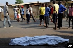 FILE - The body of a man killed is laid on a street in Bujumbura, Burundi after polls opened for the presidential elections Tuesday, July 21, 2015. Violence began in April after President Pierre Nkurnziza announced he would seek a third term in office, which the