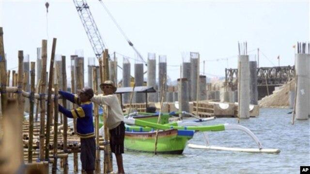 Dua orang petugas tengah membangun jembatan bambu di dekat pembangunan jalan di Kuta, Bali (Foto: dok). Para pengamat memprediksi di tahun 2013 ini masi akan terjadi kerusuhan di berbagai daerah terkait pelaksanaan otonomi daerah.