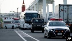 一輛據信載有鑽石公主號遊輪乘客的大巴車在警車開道下離開日本橫濱港。 (2020年2月19日)