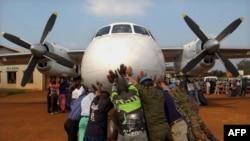 Des volontaires congolais poussent un avion de l'ONU le 25 juillet 2002