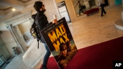 FILE - A spectator arrives at the Maria Victoria cinema to watch ''Mad Max. Fury Road'' during the 63rd San Sebastian Film Festival, in San Sebastian, northern Spain, Sept. 18, 2015.